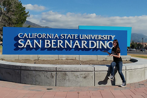 Female O U National Student Exchange study away student posing with a blue sign that reads California State University San Bernardino in white writing