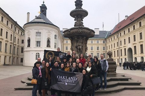 group of study abroad students holding the Oakland University flag in front of a fountain in a town square