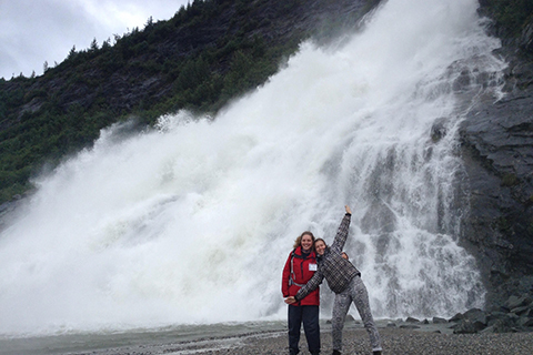 two students posing at the bottom of Nugget Falls in Alaska