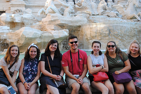 group of students seated on a bench in front of a sculpture and waterfall in Italy