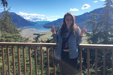 Female O U National Student Exchange study away student standing on an overlook with mountains in the background in Juneau, Alaska