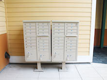 beige mailboxes in front of a yellow wall