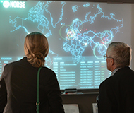 two people looking at a screen with a neon outline of a world map and lines of text beneath it