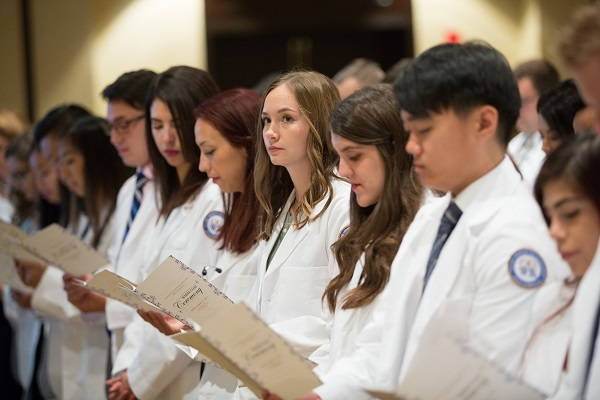 Students stand, holding programs, at the white coat ceremony.