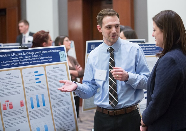An M4 presents his research poster to a faculty member at the annual Capstone Colloquium
