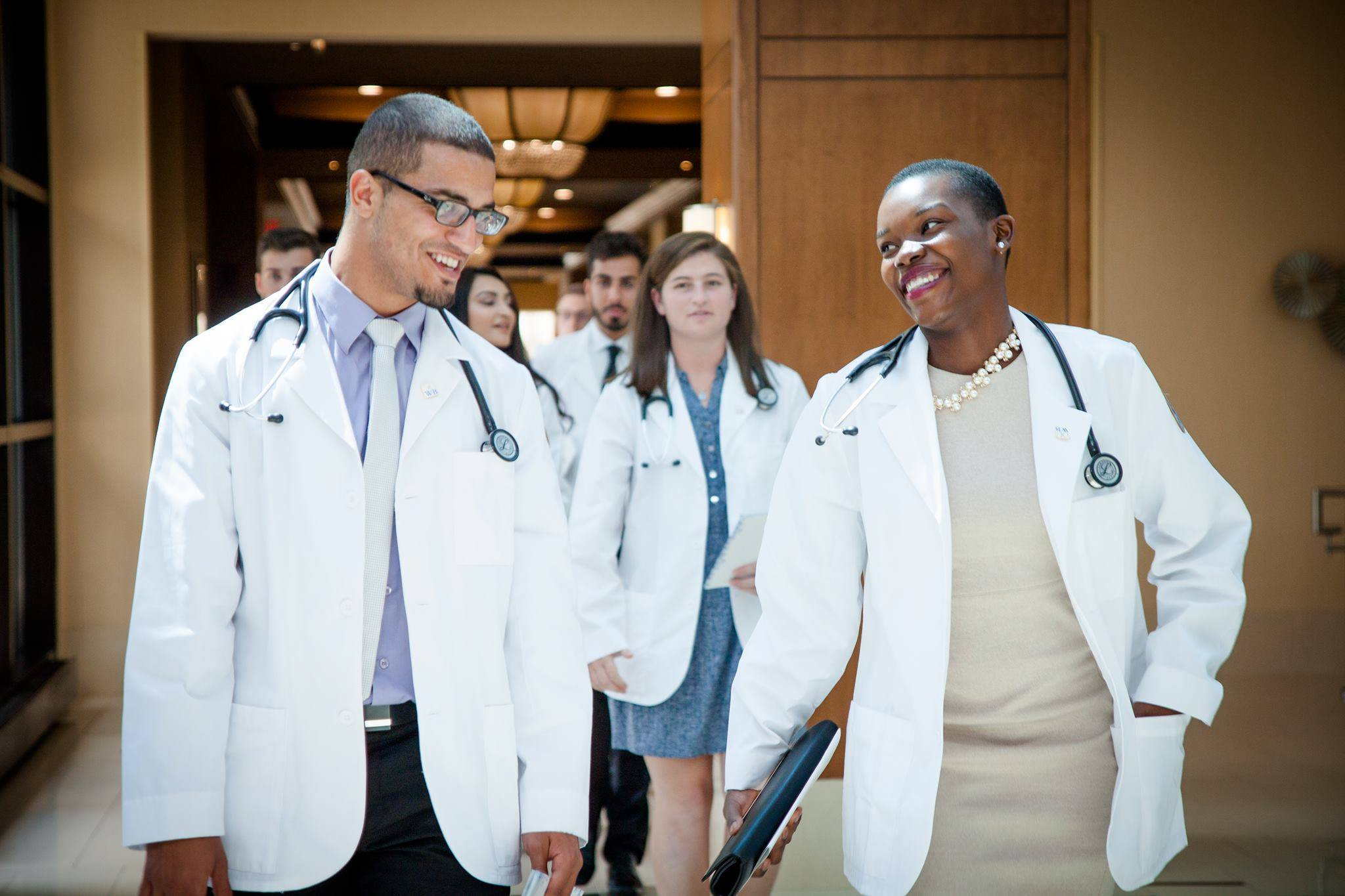 Two students walk out of the White Coat ceremony wearing their coats.