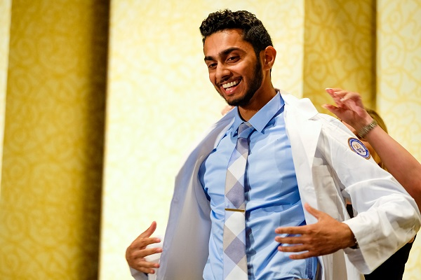 A student has help putting on his white coat on stage at the White Coat Ceremony.