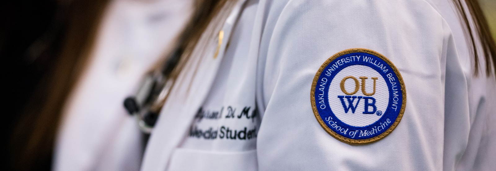 A close-up photo of a white coat with the OUWB patch in focus.