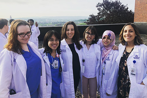 six women in white lab coats standing on a rooftop