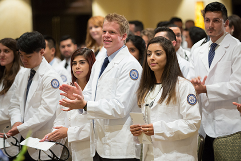 O U W B medical school students wearing white lab coats at a ceremony