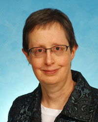 Headshot of Dr. Barbara Ducatman wearing a blazer in front of a blue background