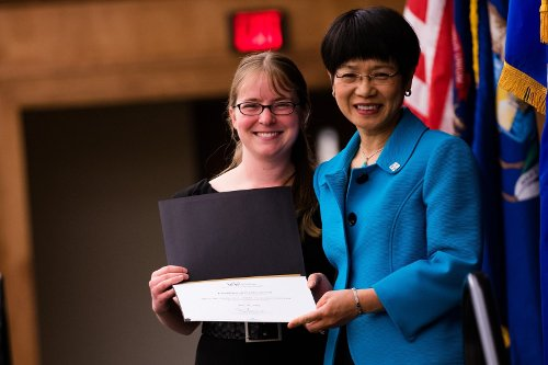 Misa Mi accepts an award from Stephanie Swanberg at OUWB Honors Convocation