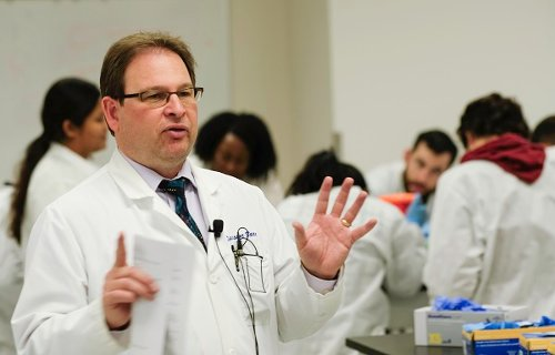 Dwayne Baxa wears a white coat and teaches a group of students at a lab table