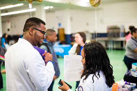 Joseph Aderemi and Keri Jones wearing white lab coats at the Chandler Park Academy Health Fair and Taste Fest