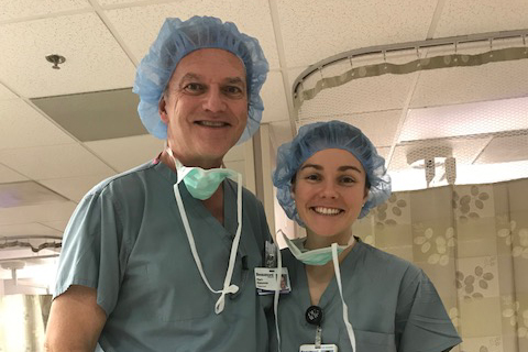 Mark and Sarah Dykowski in scrubs and hair nets in a hospital