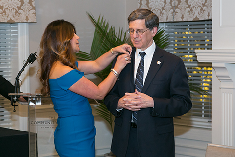 Woman placing a pin on the lapel of Dr. Robert Folberg, M.D.