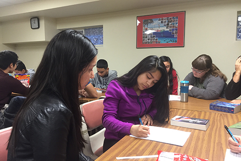 Hispanic Outreach Services mentors helping students with homework in a classroom