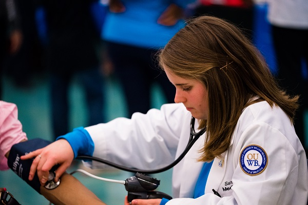 An OUWB student takes someone's blood pressure at the annual Health Fair and Taste Test