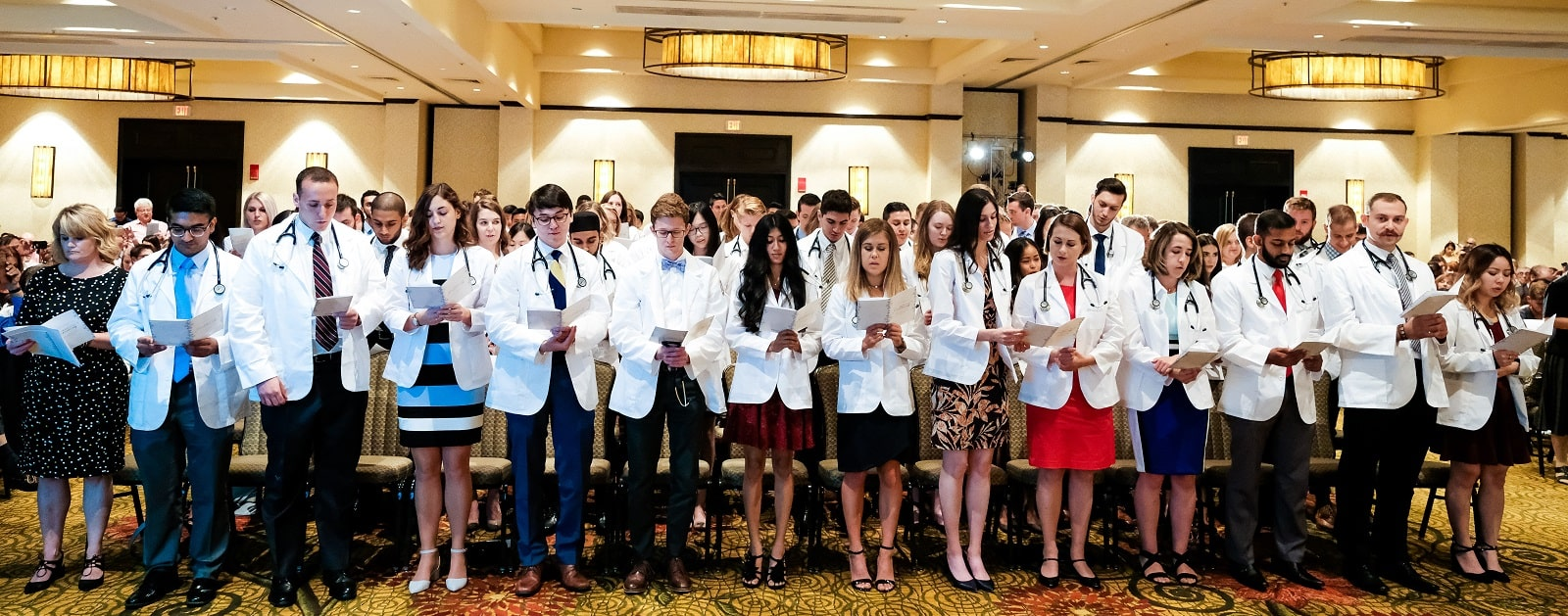 A photo of all the M1 students standing at their seats at the White Coat ceremony. They are reading from their programs.