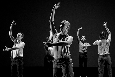 black and white image of 5 dancers on stage with one arm raised