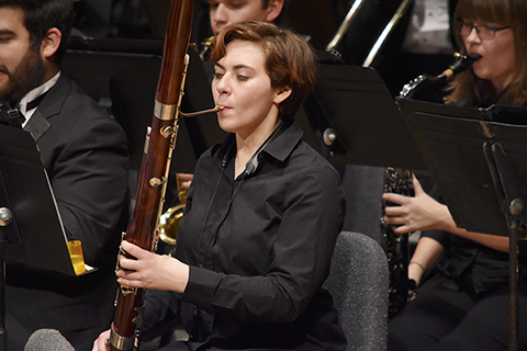 members of the wind symphony and symphonic band, seated playing instruments