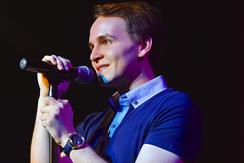 Man in a blue sweater holding a microphone on a stand