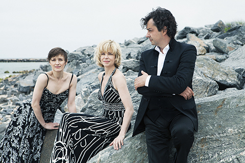members of Trio Solisti in black and white clothing on rocks by water outdoors