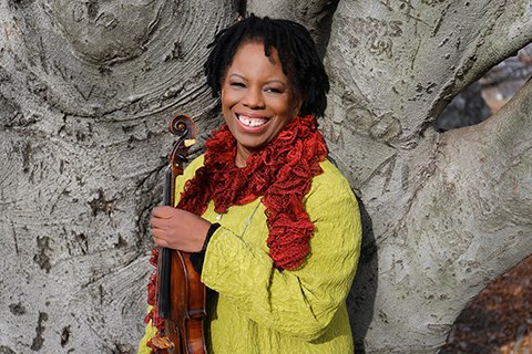 woman in a yellow jacket and red scarf, smiling while holding a violin
