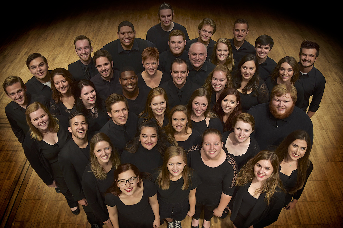 Oakland Chorale members all dressed in black, standing on a wooden floor looking up at the camera