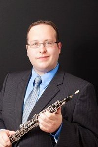 man in a suit, holding an oboe, smiling at the camera