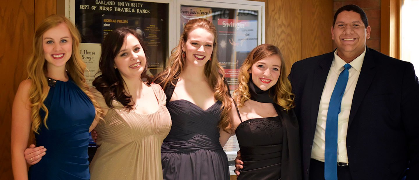 five people in evening attire, standing in a row with arms around each other, smiling at the camera