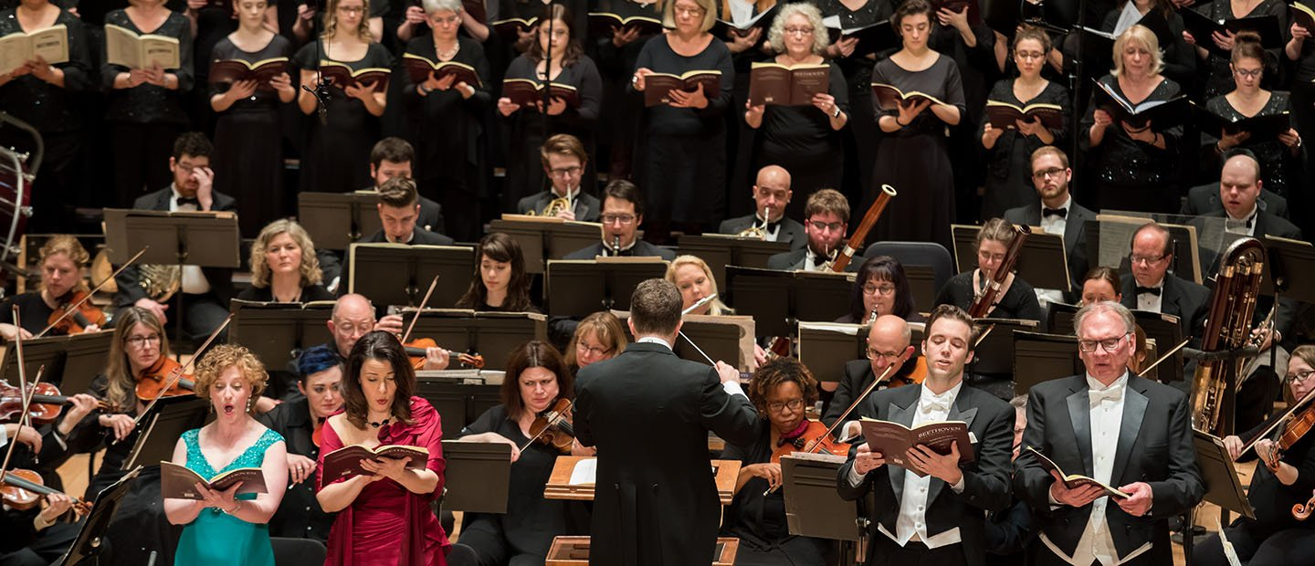 conductor in front of a large ensemble of singers and musicians playing instruments