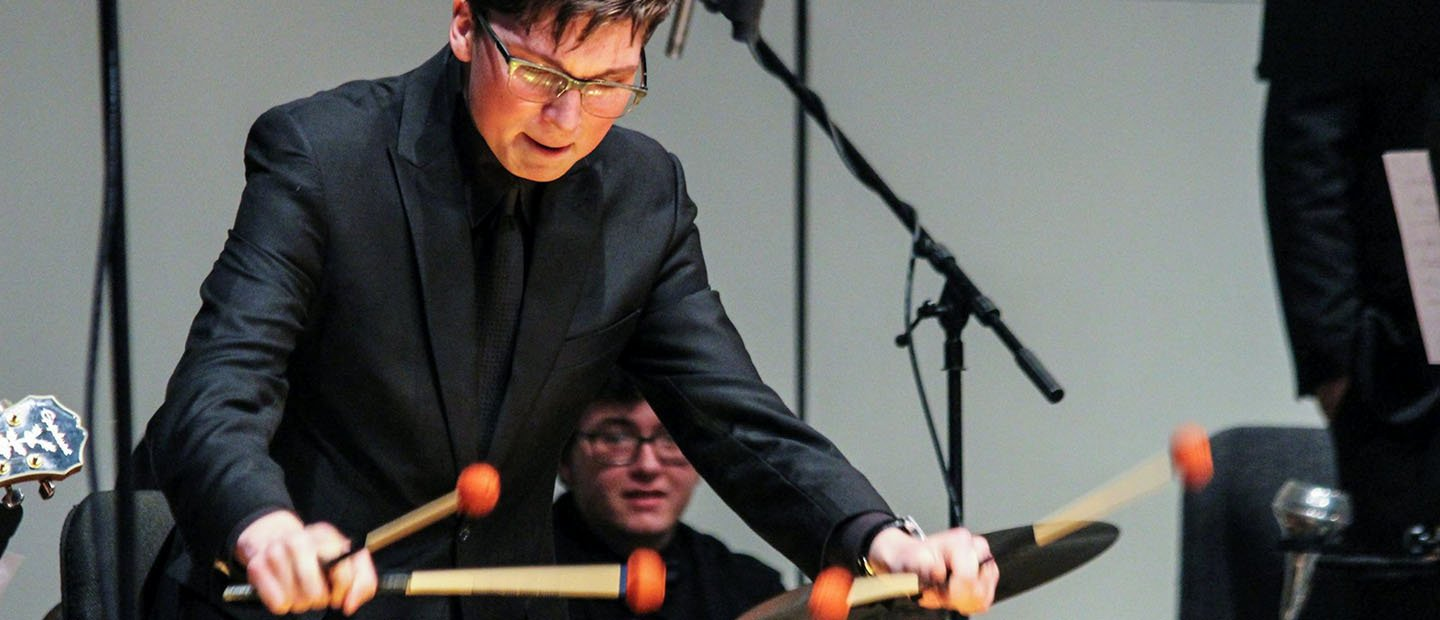 man in a black suit playing an instrument with 4 mallets in his hands