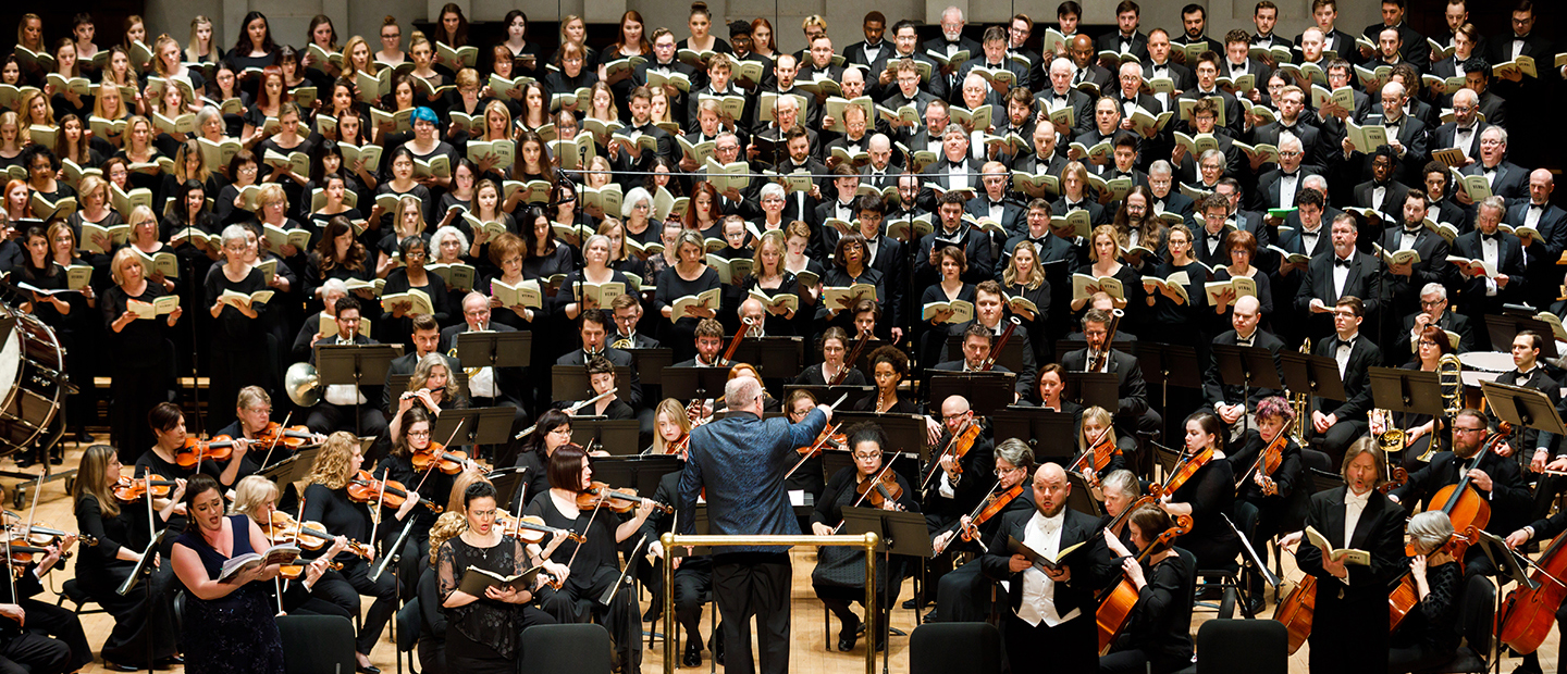 image of a large symphony orchestra and choir performing onstage