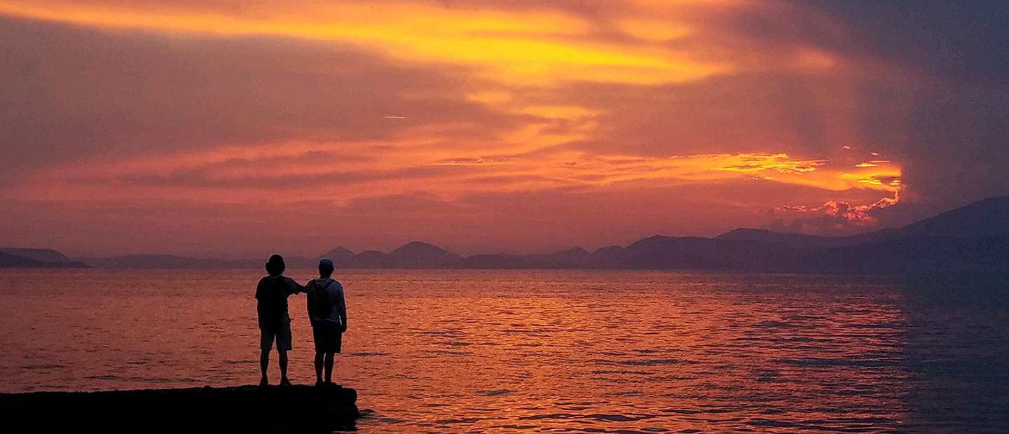 image of two people facing a sunset over a large body of water