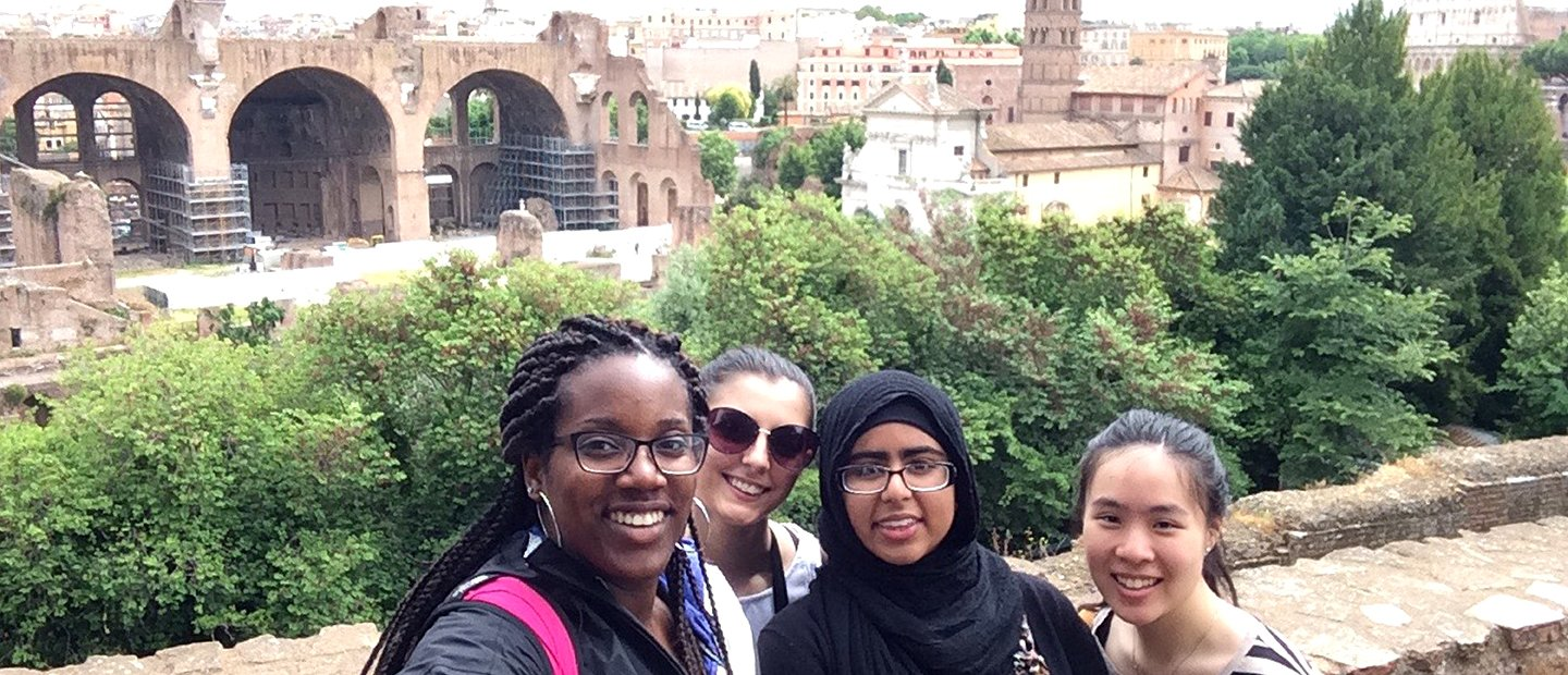 group of students standing on ledge overlooking a city in Italy