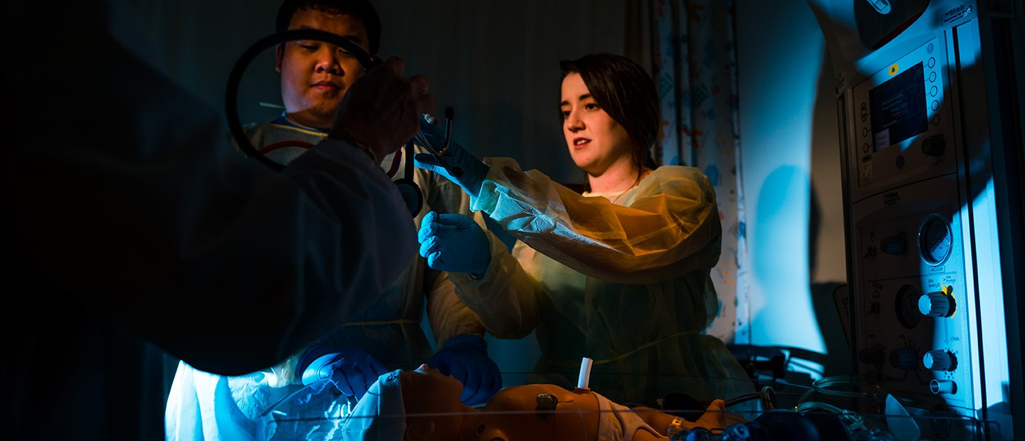 two students practicing with medical equipment in a dark room