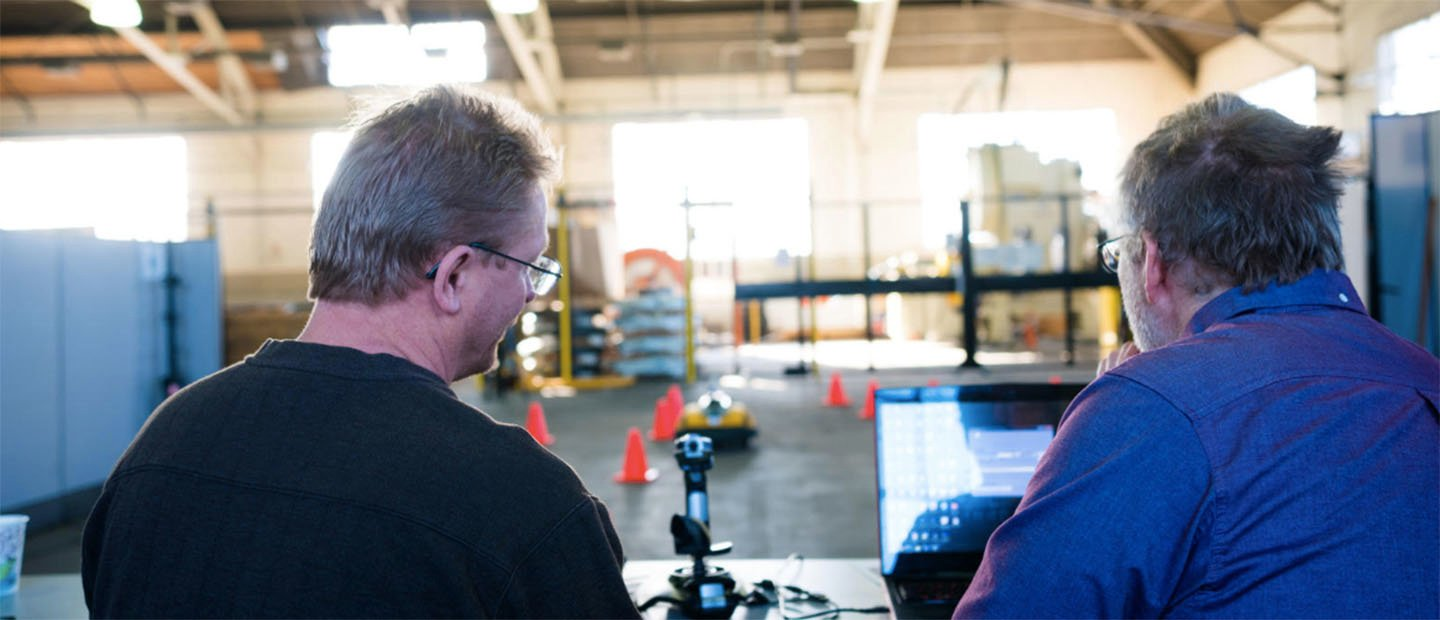 Two men operating a small remote controlled vehicle in a warehouse.