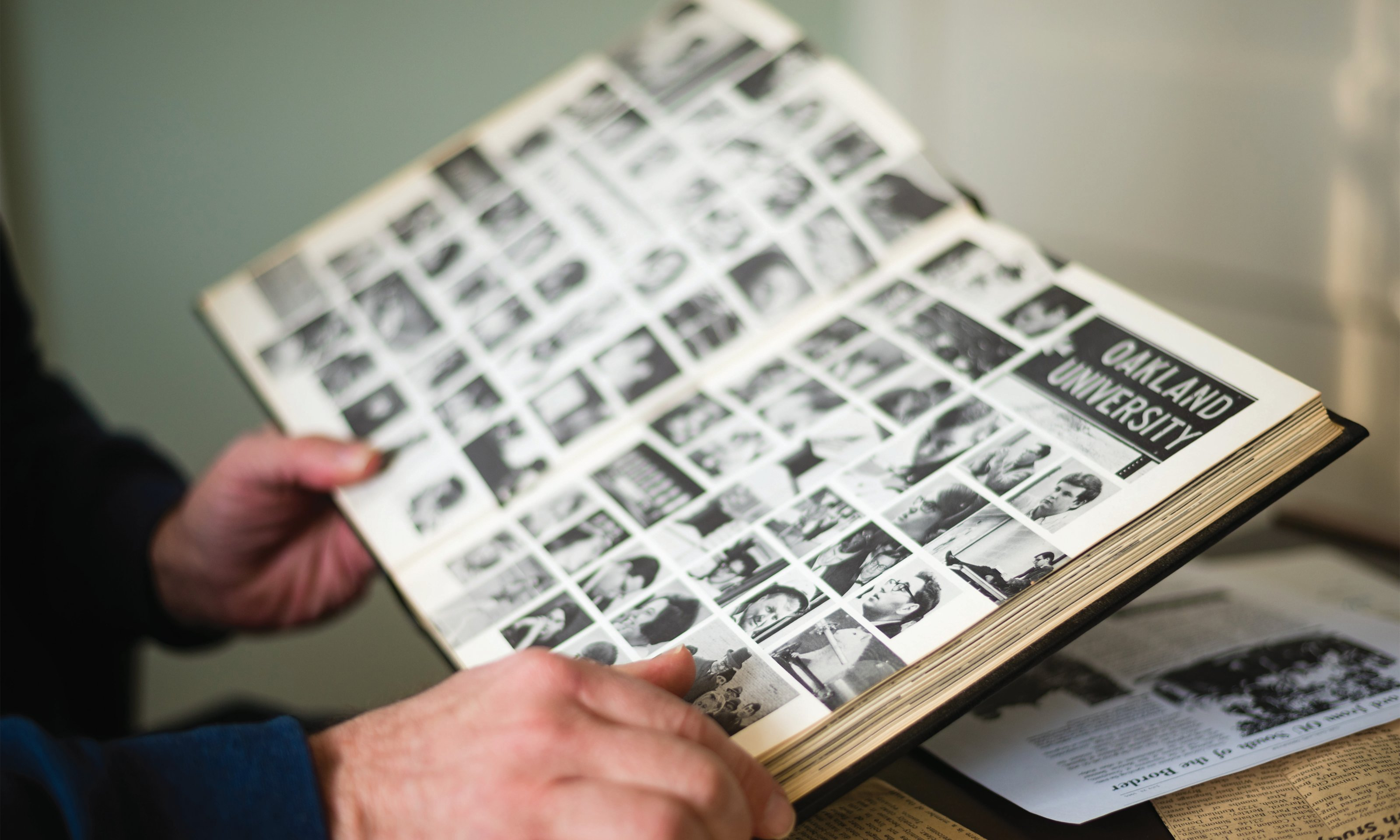 Marty Reisig's hands hold an old Oakland University Pioneer yearbook
