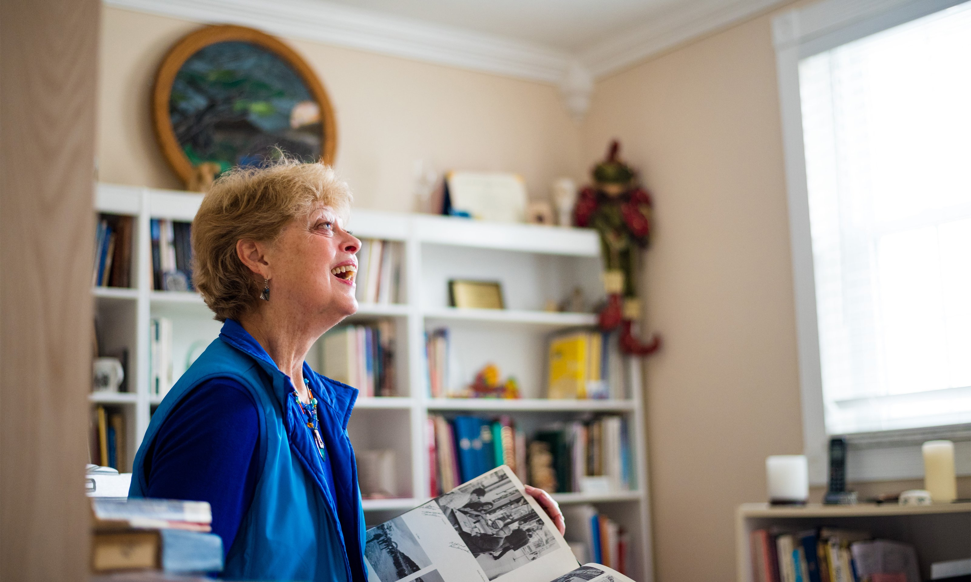 Oakland University alumna Kate Thoresen looks at an old yearbook in her home