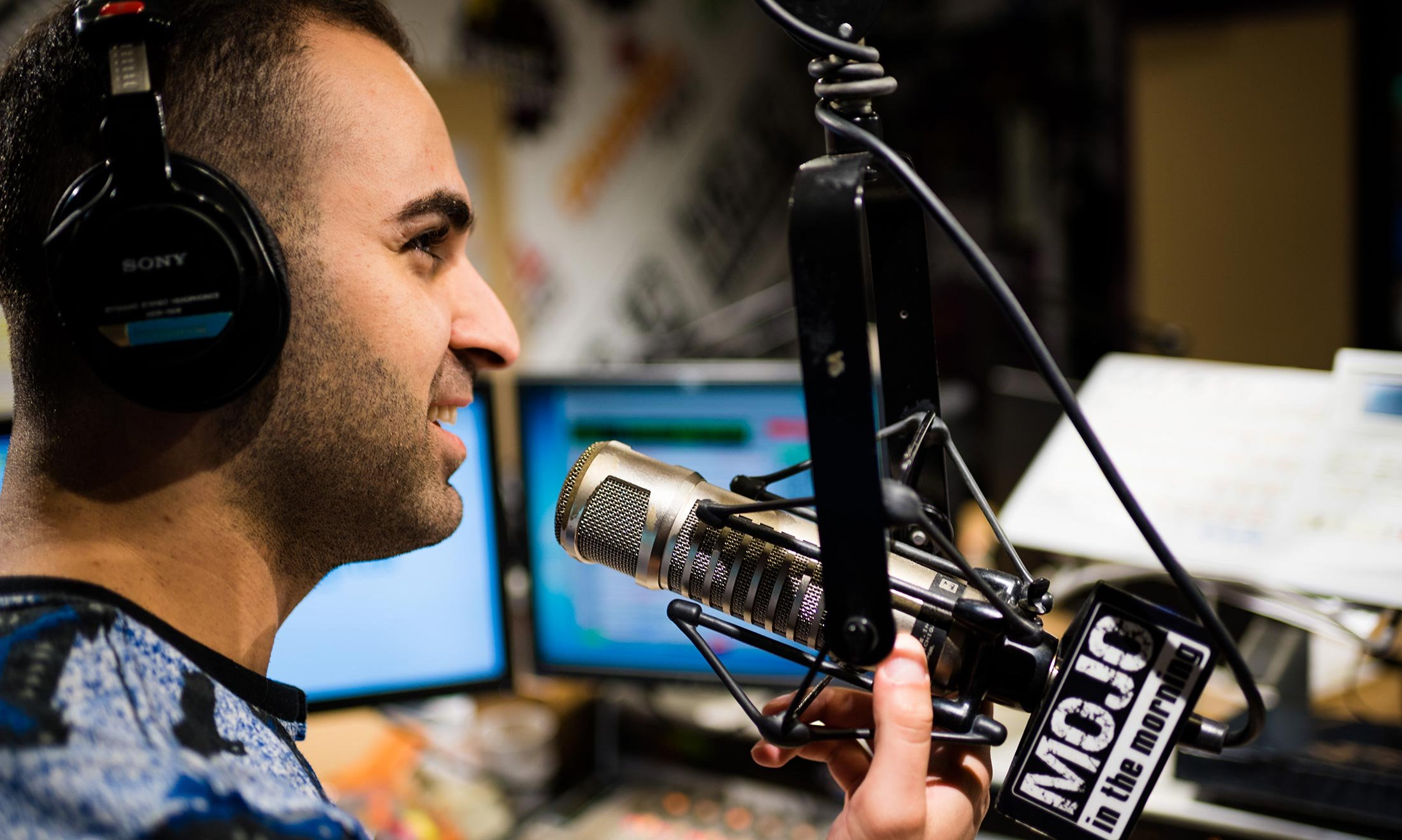 Joe Namou listens for sound with his headphones in the iHeartRadio studio