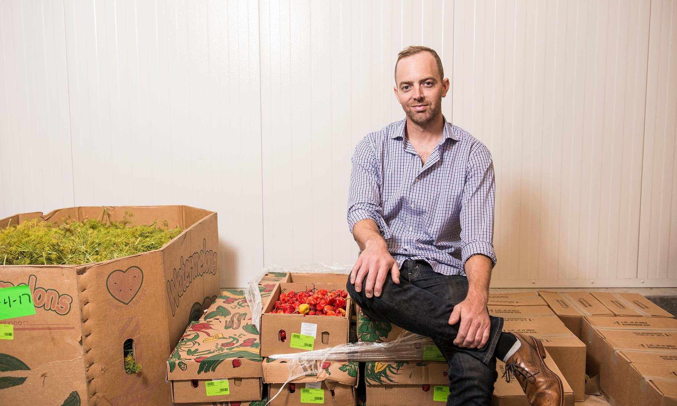 Joe McClure sits in the McClure Pickles warehouse next to fresh dill and peppers