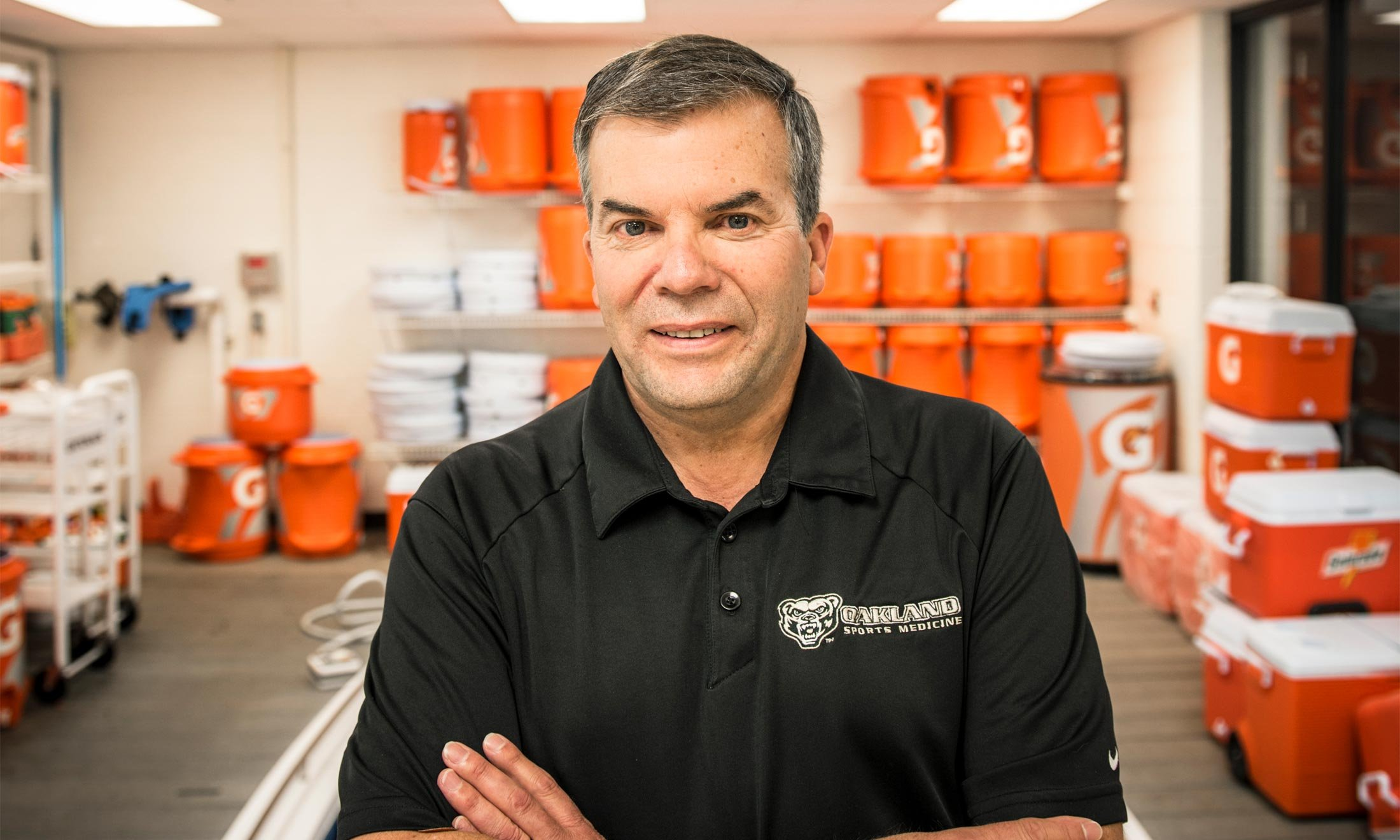 Oakland University athletics trainer Tom Ford stands in front of orange water coolers in a water training room