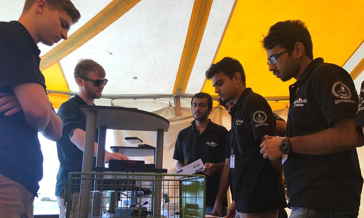Students discuss their projects for the IGVC competition at Oakland University under a yellow tent