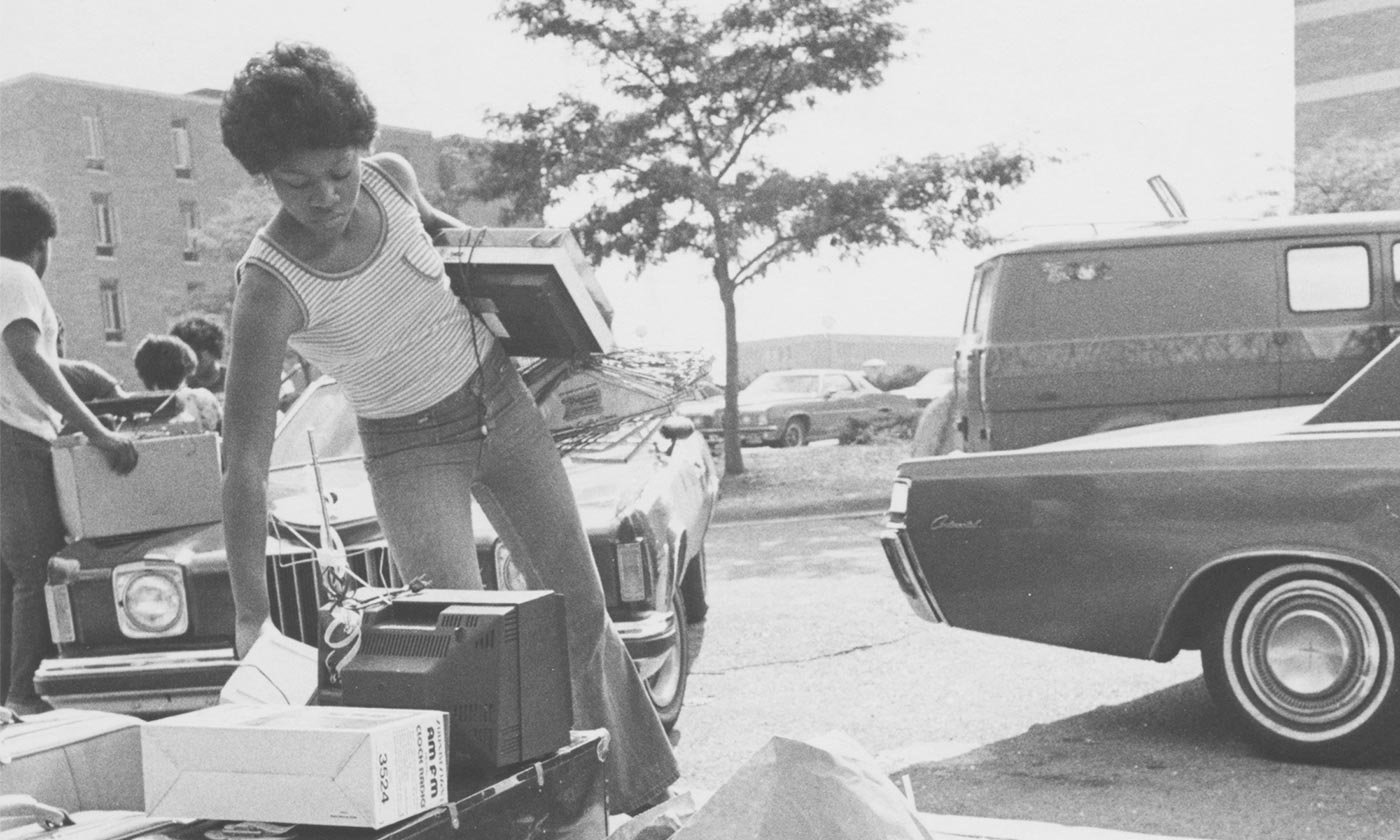 A black and white photo of an African-American Oakland University student picking up her belongings from the curbside to move into her dorm