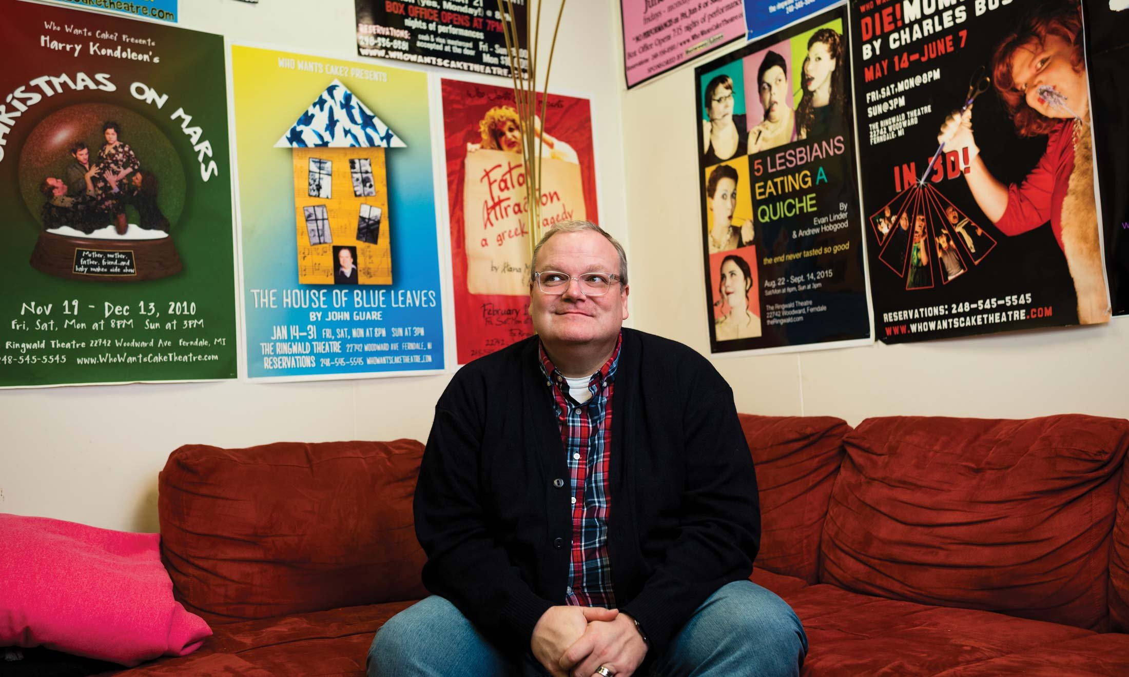 Backstage at The Ringwald Theatre in Ferndale, Michigan, Joe Bailey sits on a red couch in his office. Many posters from his shows line the walls. Wearing a black jacket, jeans and a flannel shirt.