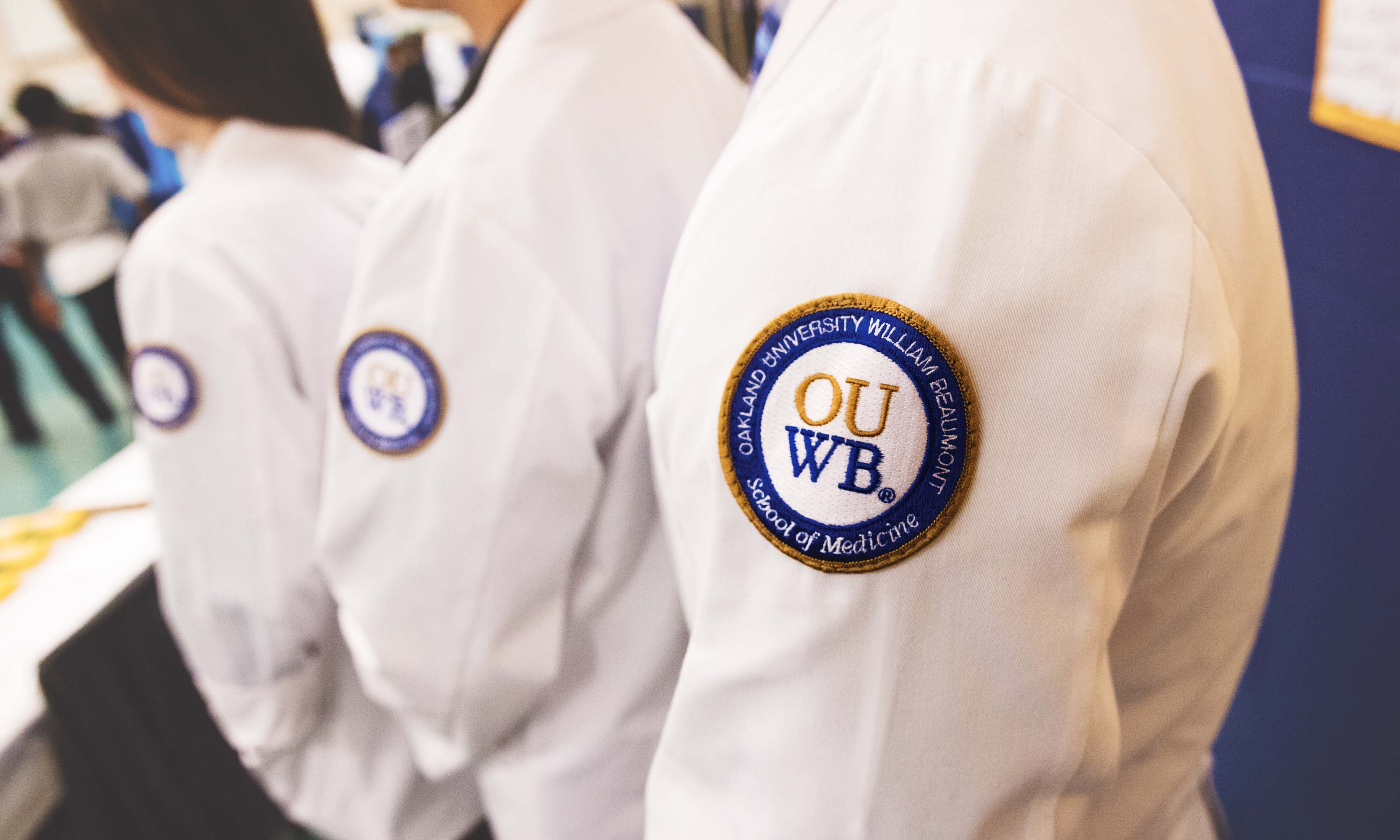 O U W B students in white coats. The O U W B logo crest is in the front of the photo, on the white coats.