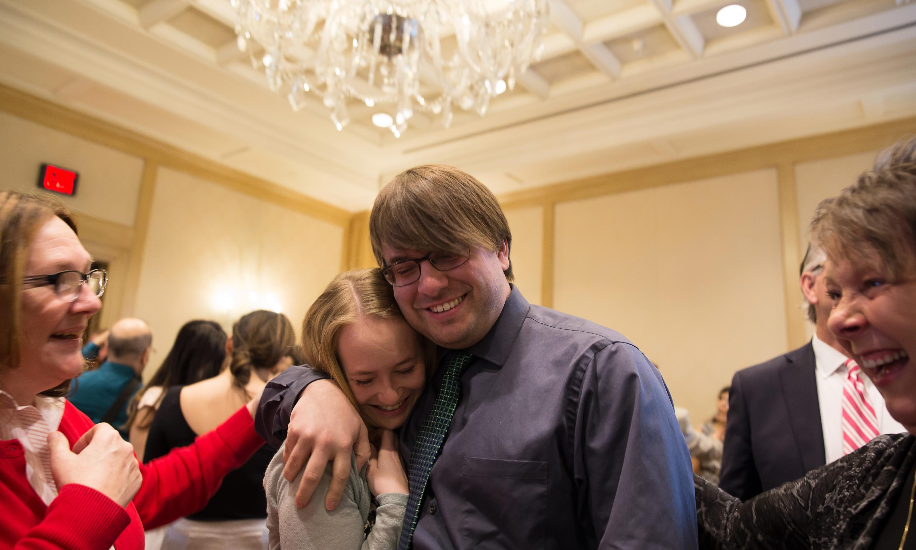 O U W B student celebrating his residency match at the Match Day 2017 ceremony, held at The Townsend Hotel in Birmingham, Michigan. Hugging a female friend in a banquet room.