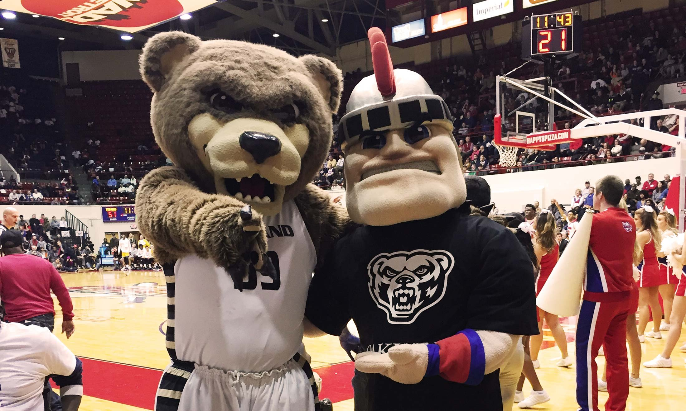 Oakland University's mascot Grizz and Detroit Mercy's mascot Tommy Titan pose together in Calihan Hall. Tommy Titan is wearing an Oakland tshirt.