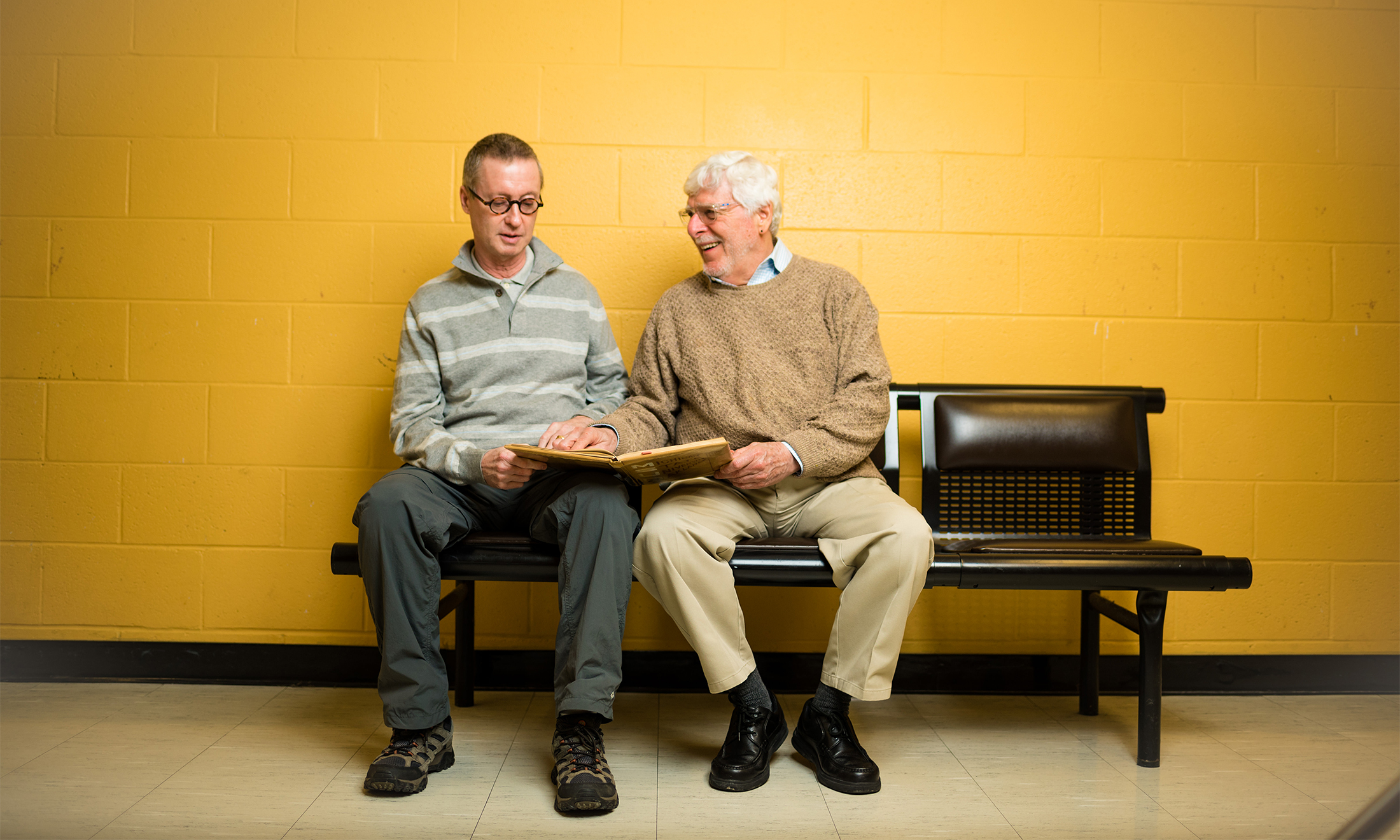 Oakland University alumni Bruce Voss and Al Monetta sit in front of a gold wall on campus